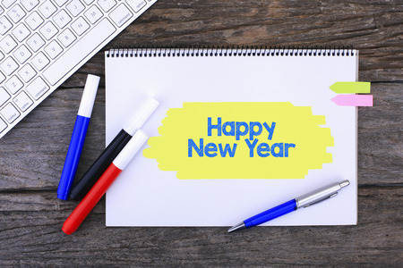 composition notebook: Notebook with Happy new year Handwritten on wooden background and Modern Computer Keyboard. Top View Composition Stock Photo