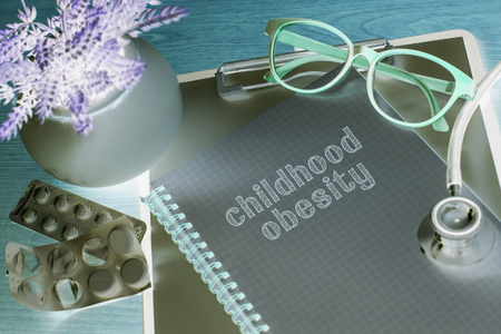 obesidad infantil: Stethoscope on note book with childhood obesity words as medical concept