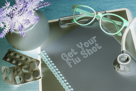 swine flu vaccinations: Stethoscope on note book with get your flu shot words as medical concept Stock Photo
