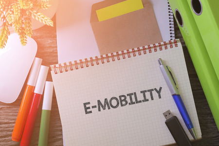 top down car: Notebook writing E-MOBILITY on table with Working space at the office with plant, usb drive and glasses
