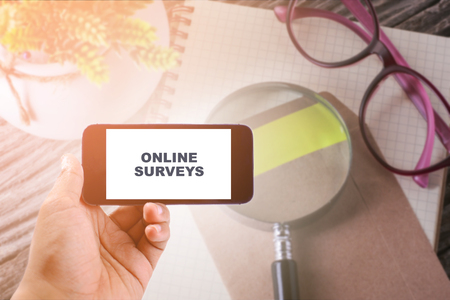 e survey: Business Concept : ONLINE SURVEYS WORD ON smartphone with office table background