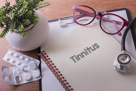 dolor de oido: Estetoscopio en el cuaderno con las palabras de tinnitus como concepto médico