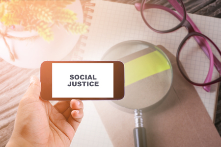 race relations: Business Concept :  SOCIAL JUSTICE WORD ON smartphone with office table background