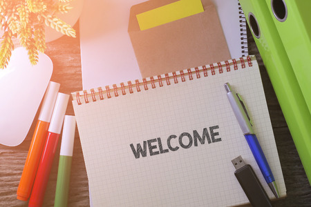come home: Notebook writing WELCOME on table with Working space at the office with plant, usb drive and glasses Stock Photo