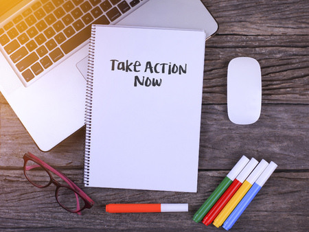 Notebook writing Take Action Now, Office table with laptop ,coffee cup,glasses Stock Photo