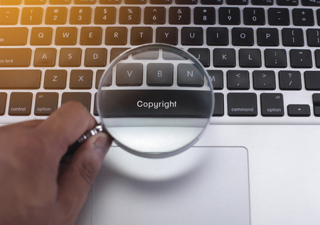 patent key: Copyright button on a keyboard with hand holding a magnifying glass Stock Photo