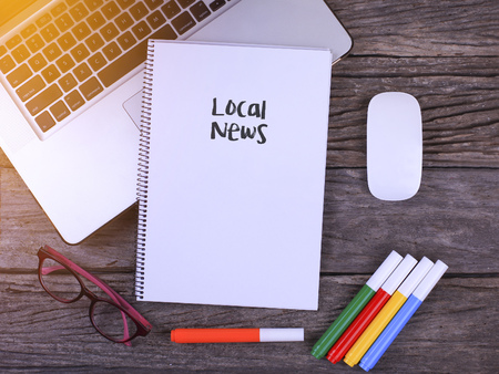 small articles: Notebook writing Local News, Office table with laptop ,coffee cup,glasses Stock Photo