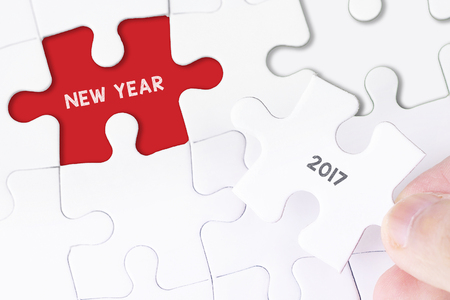 initiatives: Female hand and missing puzzle with NEW YEAR 2017 WORD