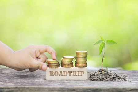 ROADTRIP WORD Golden coin stacked with wooden bar Stock Photo