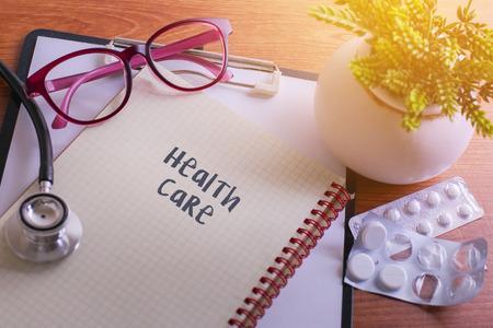 Stethoscoop op notaboek met Gezondheidszorgwoorden als medisch concept