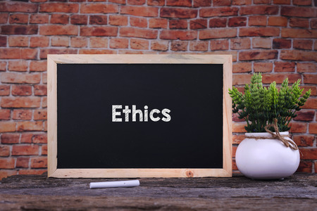 Ethics word on blackboard with green plant Stock Photo