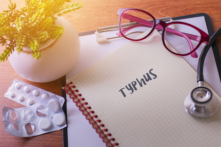 typhus: Stethoscope on note book with Typhus words as medical concept
