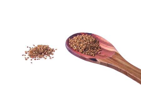Fenugreek seeds on a brass spoon isolated on a white background Stock Photo