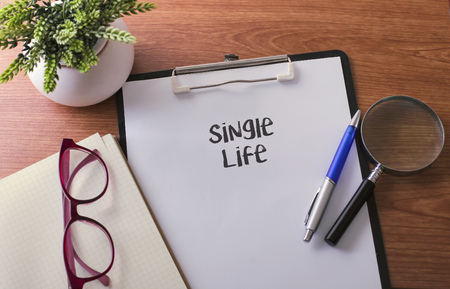 Single Life word on paper with glass ballpen and green plant