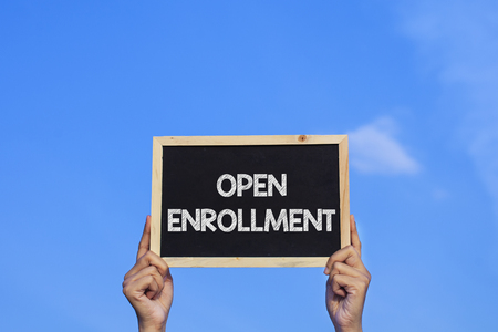 OPEN ENROLLMENT/ Man holding small blackboard on blue sky background