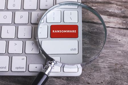Bedrijfsconcept: RANSOMWARE op computertoetsenbord op houten achtergrond met copyspacegebied