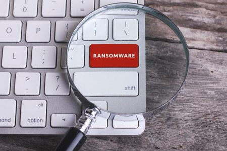 Business concept: RANSOMWARE on computer keyboard on wooden background with copyspace area