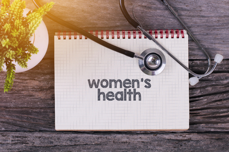 Women's Health word on notebook,stethoscope and green plan