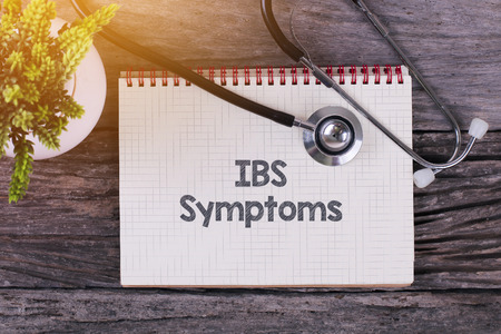 ibs: IBS Symptoms word on notebook,stethoscope and green plan