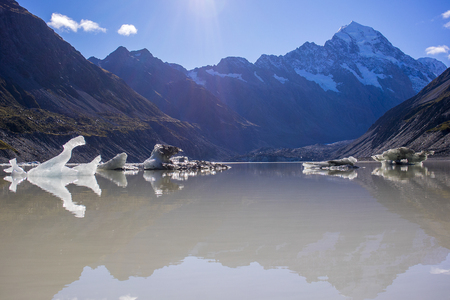 frozen lake: Tasman Glacier Lake with giant floating icebergs, Aoraki Mount Cook National Park New Zealand. Mt Cook looming in the clouds Stock Photo