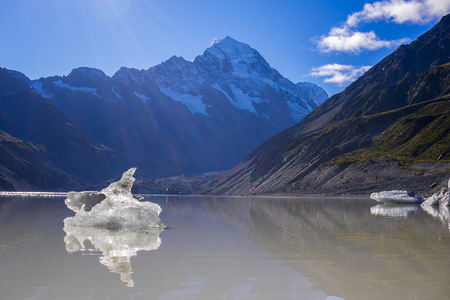 Tasman Glacier Lake with giant floating icebergs, Aoraki Mount Cook National Park New Zealand. Mt Cook looming in the clouds Stock Photo