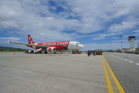 Suratthani ,Thailand-MAY20, 2017: Passenger airplane-Airasia on runway at Suratthani airport with beautiful blue sky background. An Airasia plane on runway waiting for passengers to fly to Bangkok