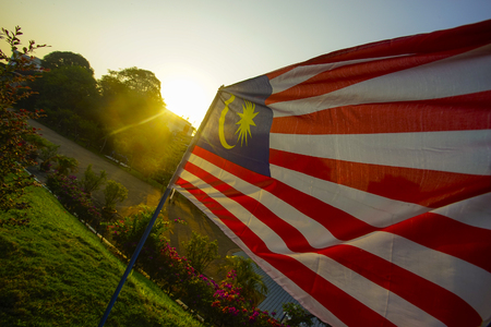 winner waving Malaysian flag against the sunset