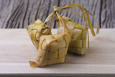Ketupat (Rice Dumpling) and curry On wooden Background. Ketupat is a natural rice casing made from young coconut leaves for cooking rice during eid Mubarak