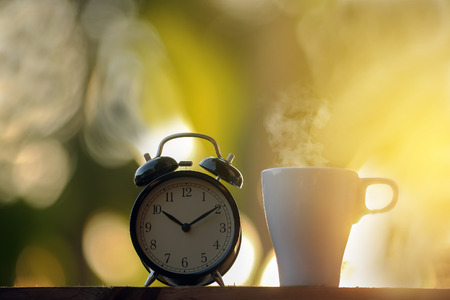 Black alarm clock and a cup of coffee on the morning
