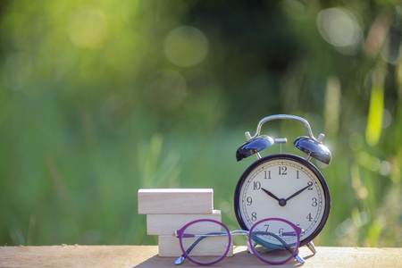 Black alarm clock stacked on wooden bar with shallow DOF green background Stock Photo