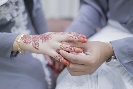 Groom put a wedding ring on bride hand