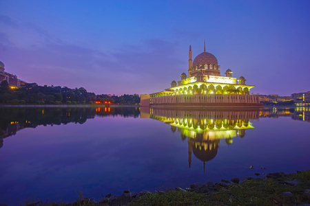 Mirror reflection of beautiful Putra Mosque in the lake during sunrise Stock Photo