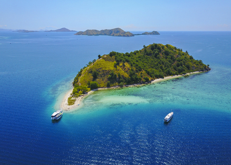 Aerial view of beautiful scenery at Flores island with tourist yatch, turqouise and dark blue sea