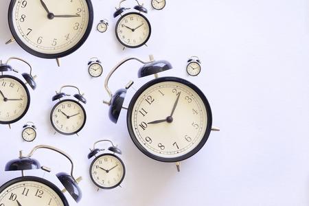 Many black alarm clock on white background. Flatlay topview