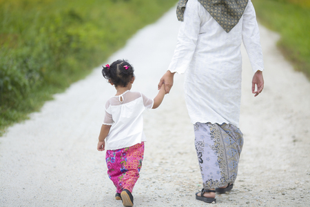 Mom holding her baby girl hand with hari raya dress.
