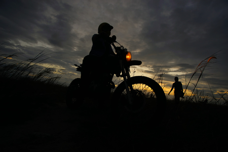 Silhouette of a man riding his motorcycle during sunset