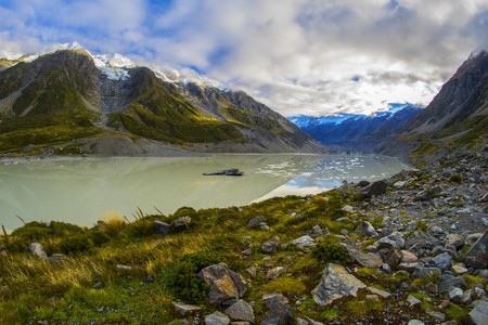 Tasman Glacier Lake with giant floating icebergs, Aoraki Mount Cook National Park New Zealand. Mt Cook looming in the clouds Stok Fotoğraf