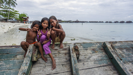 Semporna Sabah, Malaysia - July 18, 2017: Scene at Mabul Island. Sea Gypsy kids on a handmade canoes in Bodgaya Mabul Sipadan Island, Sabah Borneo, Malaysia