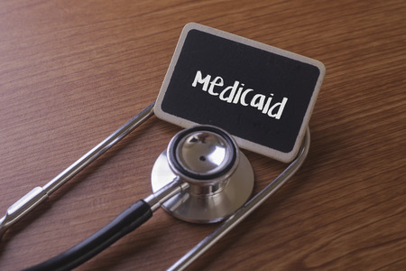 Medical Concept- Medicaid word written on label tag with Stethoscope on wood