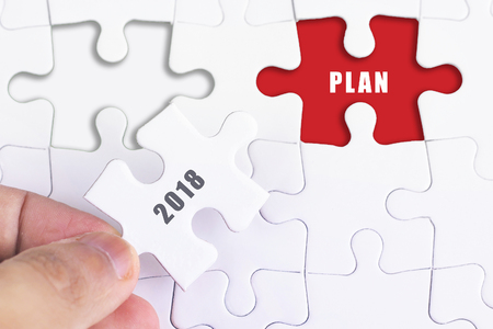 Business Concept - Female hand and missing puzzle with 2018 PLAN