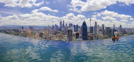 Unidentified businessman and traveller swimming in infinity pool with Kuala Lumpur City skyline