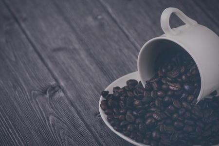 Roasted premium coffee bean in a white cup on black  and wooden