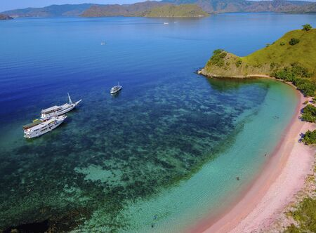 Aerial view of a Pink beach in Flores, with a tourist and a yatch.