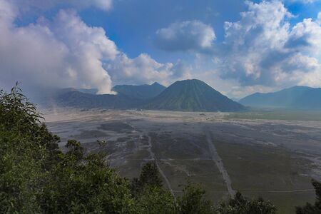 Aerial view of Mount Bromo with dramatic cloud formation and blue sky Stok Fotoğraf