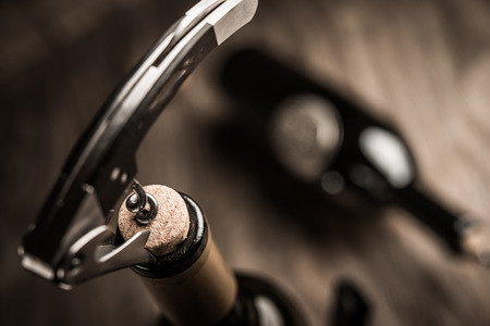 Bottle of wine and corkscrew over wooden background Stock Photo
