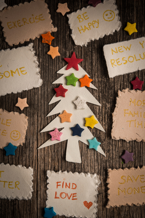 achivement: New Years resolutions and Christmas tree on vinatege wooden backgroun Stock Photo