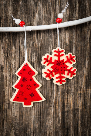 christmastide: Red Christmas decorations over rustic wood