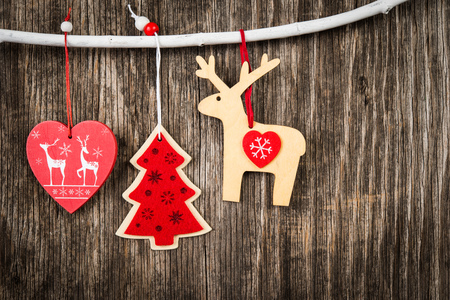 Red Christmas decorations hanging on branch over wooden background Stock Photo