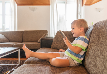 remote controls: Boy with remote controls watching television Stock Photo