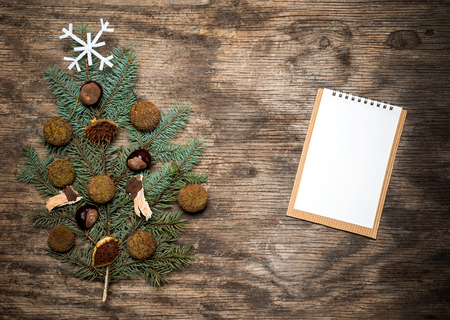 fir branch: Christmas tree made of fir branch and notepaper on vintage wooden background with copy space
